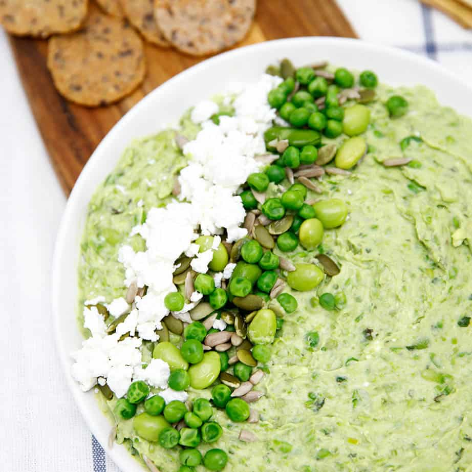 Overhead close up of smashed Bean and Pea Dip and crackers on a tea towel