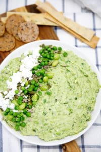 Smashed Pea and Bean Dip on a white plate with teatowel