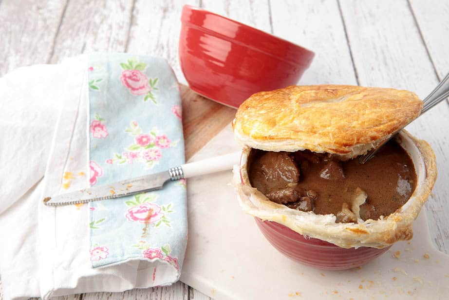 Guinness Pot Pie on a wooden background with the pastry lid partial off to reveal the filling