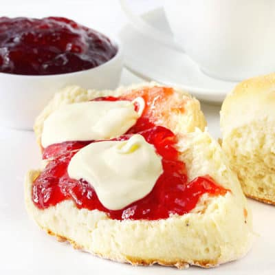 Homemade Scones with jam and cream on a white platter