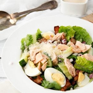 Individual serve Salmon Caesar Salad in a white bowl with dressing on the side