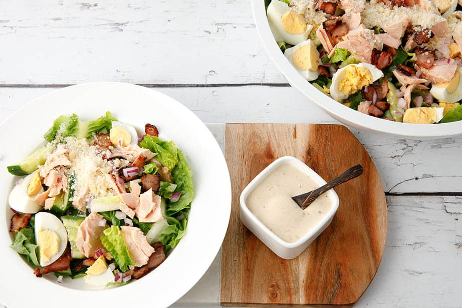 Overhead shot, white bowl of Caesar Salad with dressing on the side served from a large salad bowl