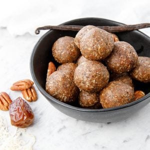 Thermomix Salted Pecan Bliss Balls on a white background, pecans and vanilla bean in photo