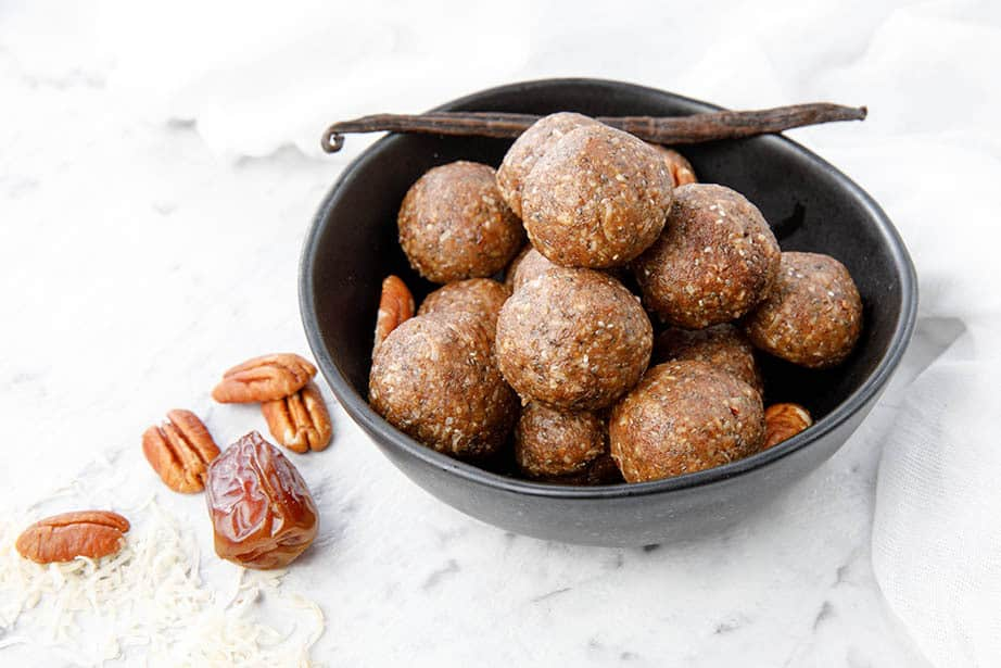 A bowl of Thermomix Salted Pecan Bliss Balls on a white background, pecans and vanilla bean in photo