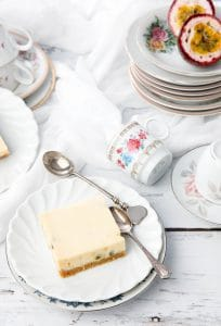 Passionfruit slice on a white wood background surrounded in a collection of crockery.