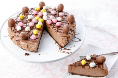 Whole chocolate cheesecake with a slice on a plate decorated in Easter Eggs