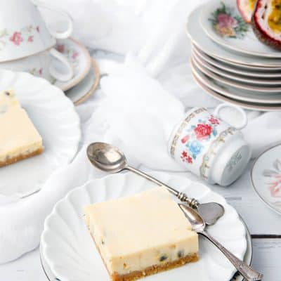 Still life of Passionfruit Slice surrounded by elegant crockery