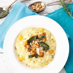 Overhead shot of pumpkin risotto in white bowl with blue napkin