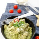 Potrait shot black bowl with chicken in a creamy pesto sauce