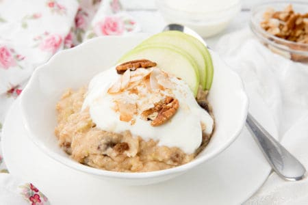 A bowl of Apple Pie Oatmeal topped with yoghurt, nuts, coconut and apple