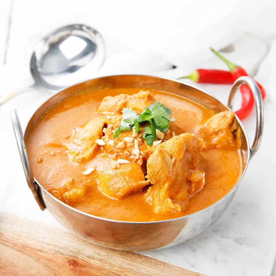Square crop chicken curry in metal bowl on a white background
