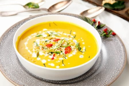 Thai Pumpkin Curry in a white bowl with herbs and chili surrounding the dish