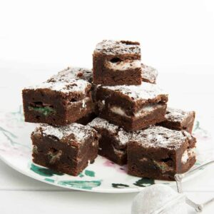 Pile of chocolate brownies on a floral plate with white background