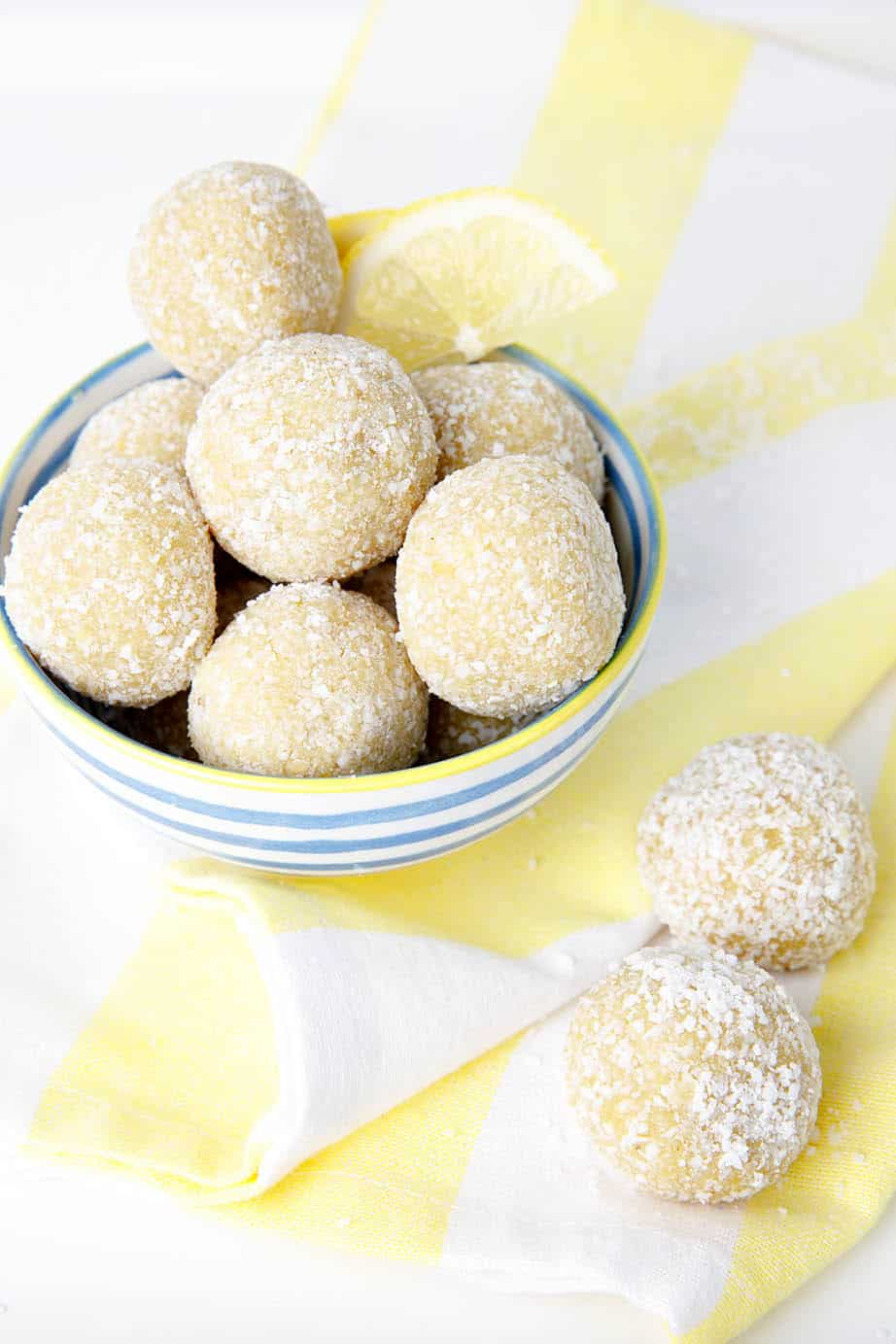 Portrait image of lemon bliss balls in a blue striped bowl on a yellow tea towel