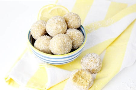 lemon bliss balls on a white background and yellow striped tea towel