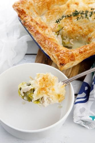 Chicken pie on a chopping board with a slice in a white bowl