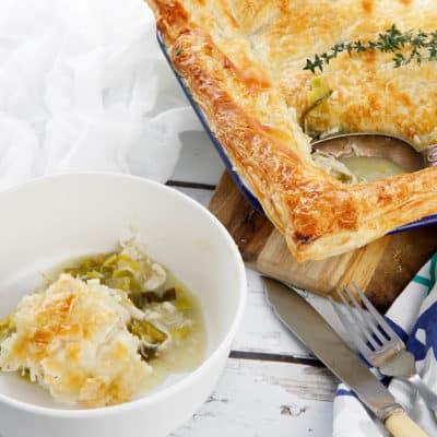 Square image chicken and leek pie on a white wood background