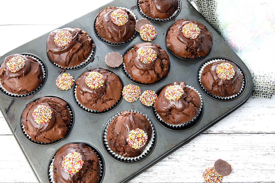 Overhead shot double chocolate muffins in a tray on a white wood background