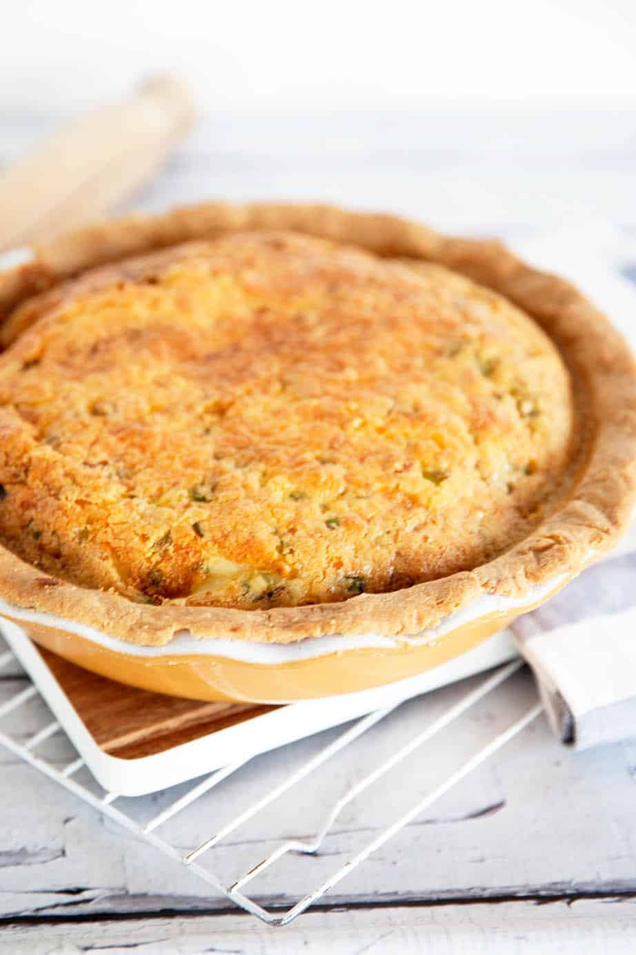 Portrait image of baked quiche Lorraine in a yellow pie dish on white cooling rack