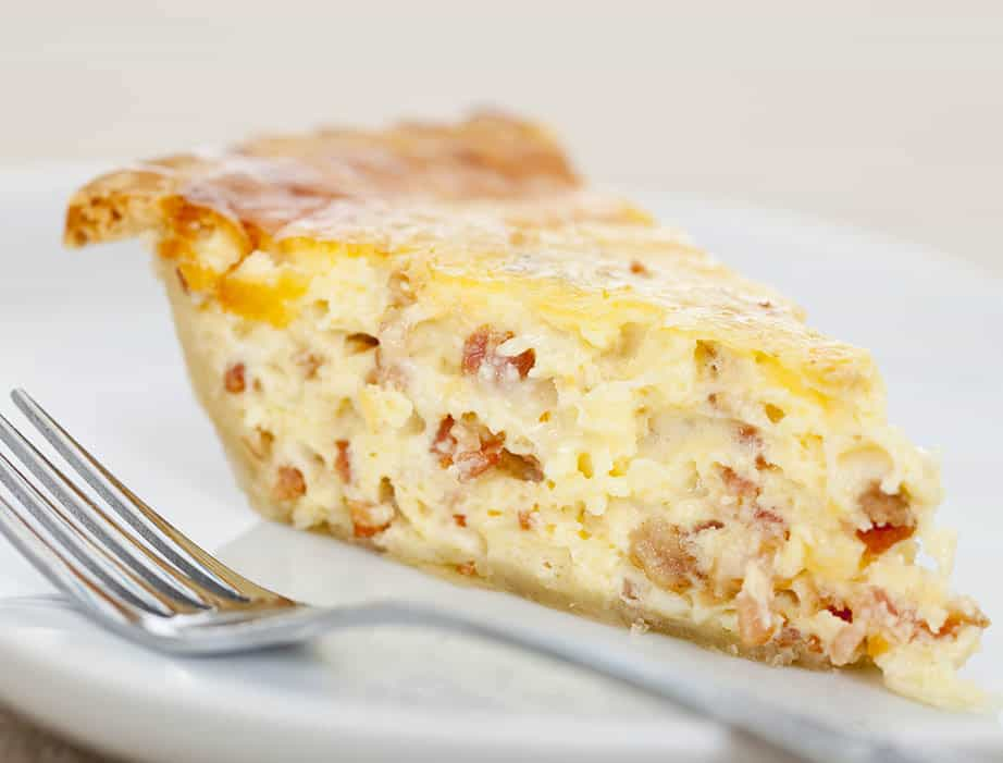 A single lice of quiche Lorraine on a white plate with fork