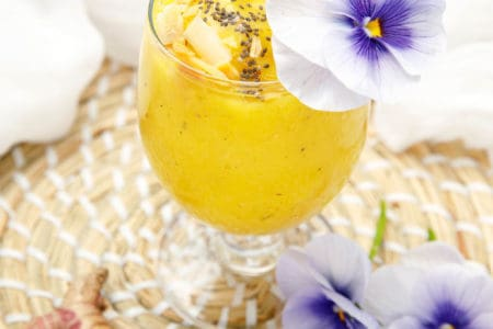 Turmeric Mango Smoothie on white background decorated with purple flowers and chia seeds