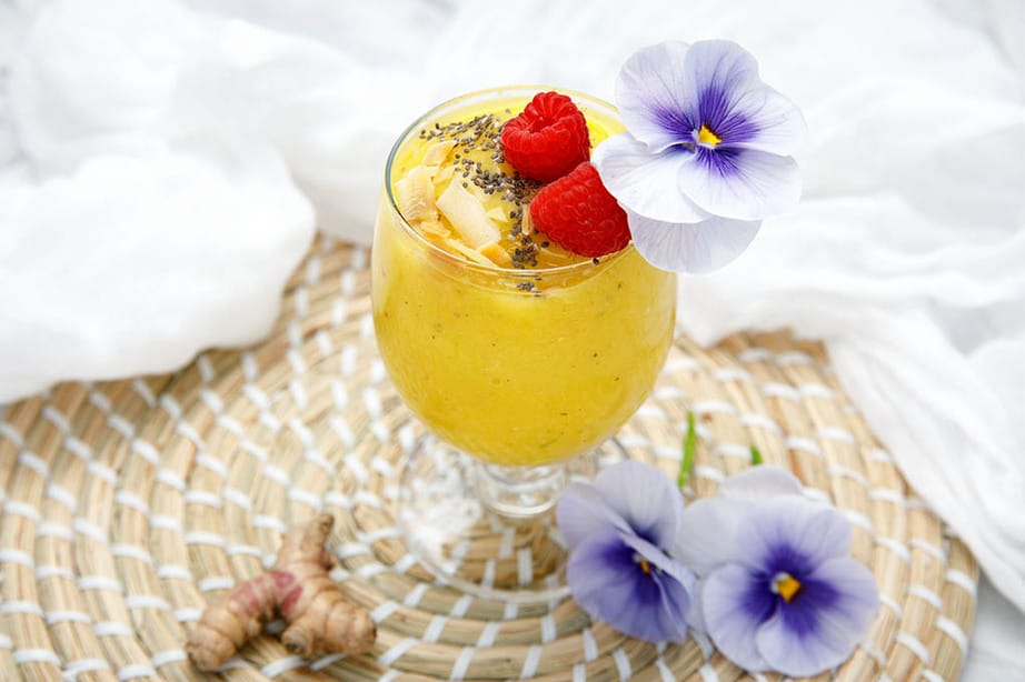 Glass containing turmeric mango smoothie decorated with raspberry and chia seeds