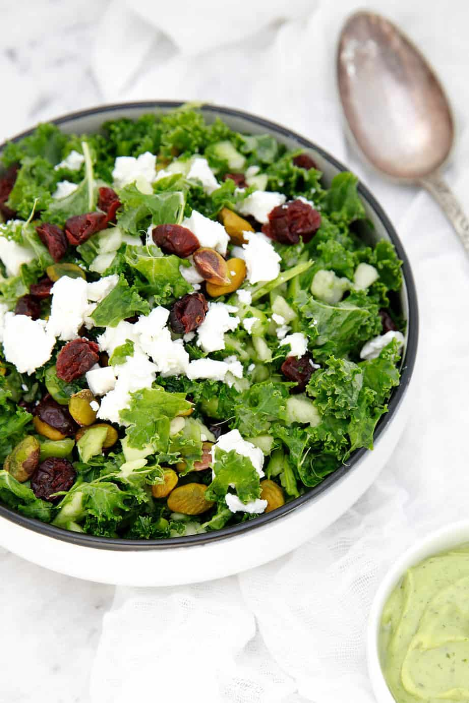 Potrait image of kale salad on a white cloth with cranberries and nuts