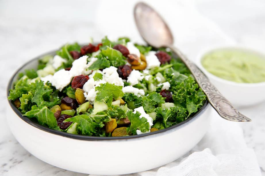 white bowl of Kale salad with cranberries on white background