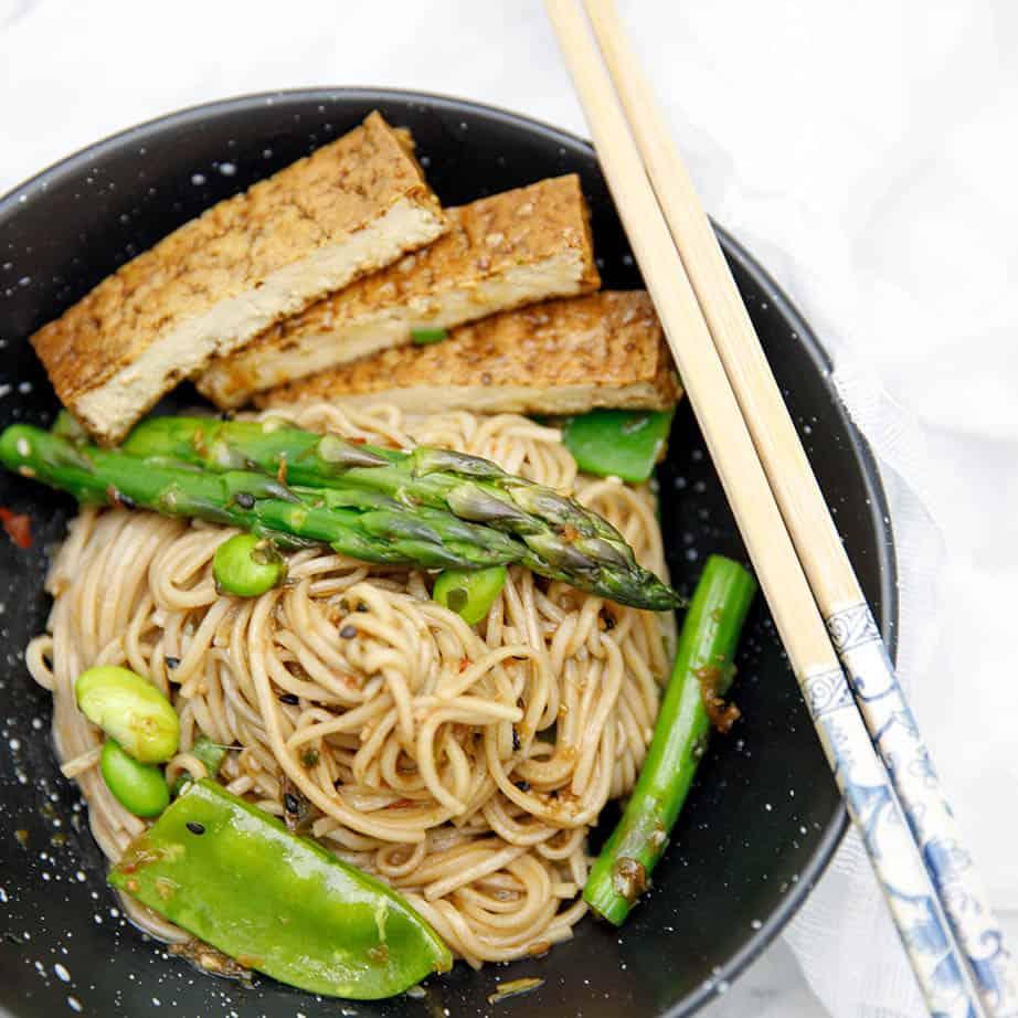 Overhead shot of Soba noodle salad in black bowl