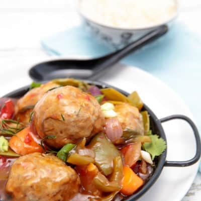 Sweet and sour pork meatballs on a black bowl white background with rice