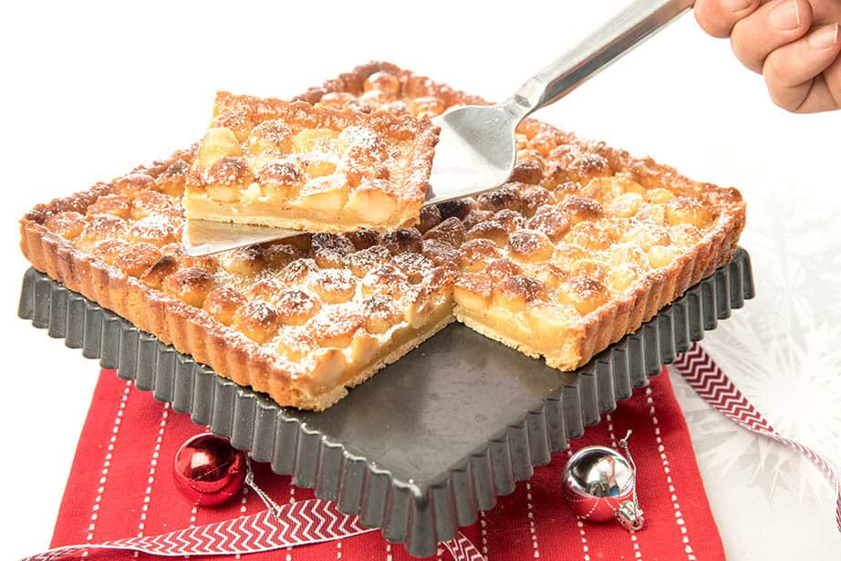 A slice of Caramel Macadamia tart being lifted from the cake tin