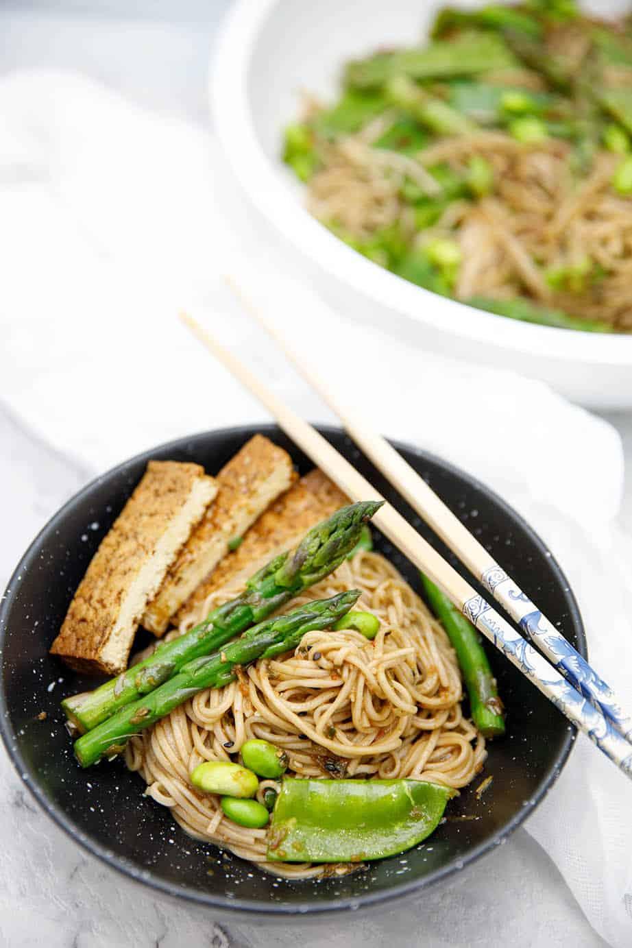 Overhead shot of soba noodle salad in black bowl on white background