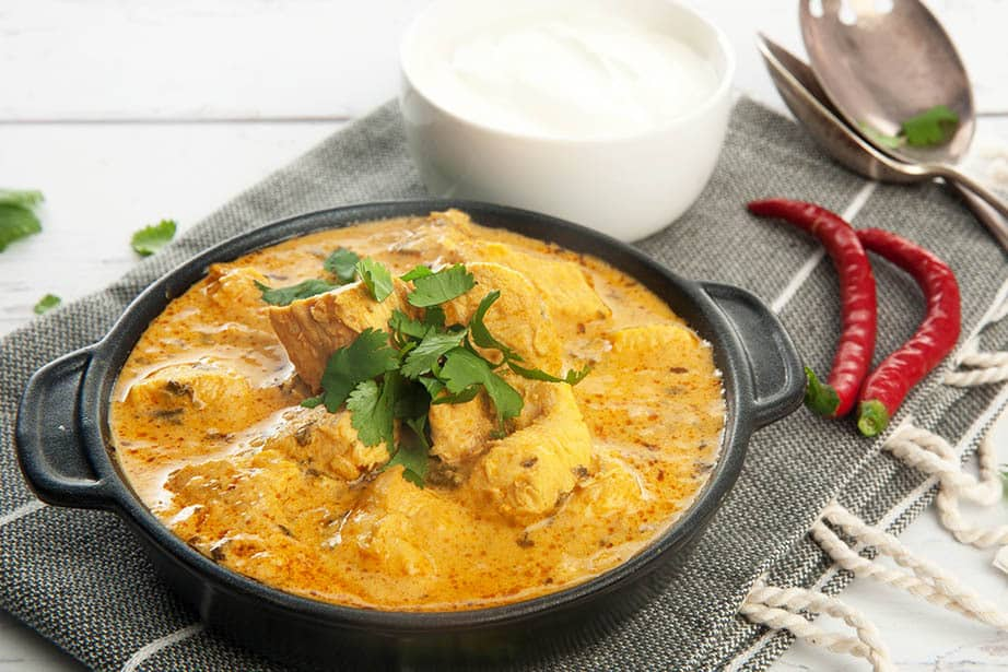 Thermomix Indian Chicken Curry on white background with yoghurt