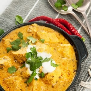 Overhead shot Easy Chicken Curry in black pan with yoghurt and chili