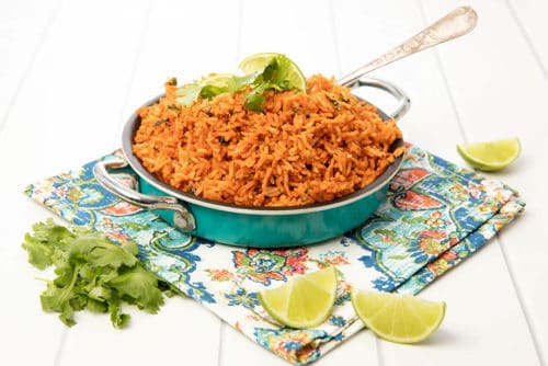 Mexican Red Rice in a blue dish on white background