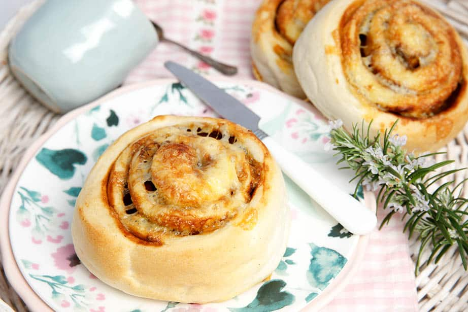 Overhead shot Cheesymite scrolls on a floral plate white knife