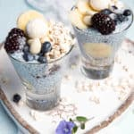 Layered blue chia puding in a glass with berries and banana