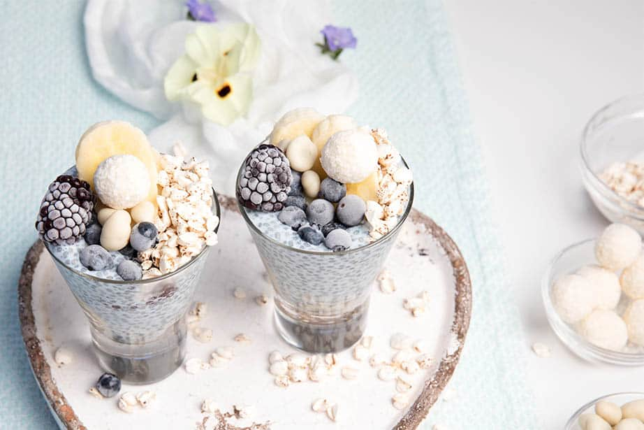 Blue Chia Puddings on a white and light blue background with berries