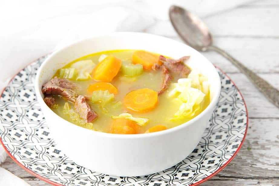 Close up white bowl with corned beef and cabbage soup