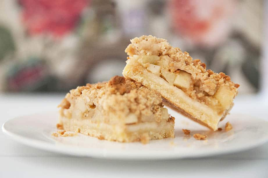 Close up image of apple slice with streusel topping against a coloured background