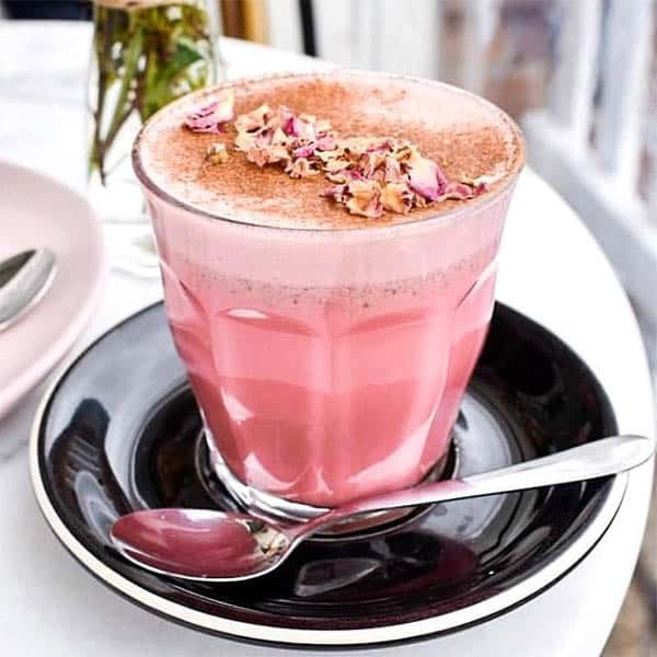 Pink Latte in a clear glass on a cafe table