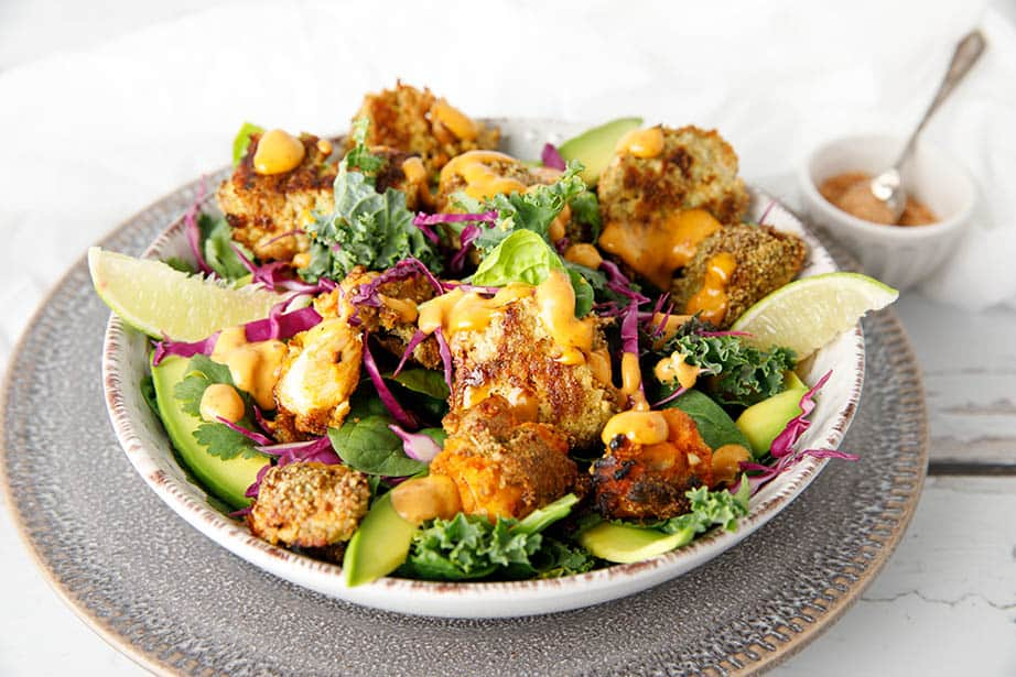 Sideview of Keto Popcorn Chicken Salad in a bowl on white background