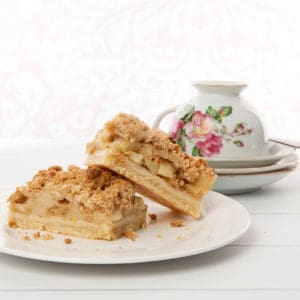 Apple Tart with Streusel topping on white background with floral tea cup