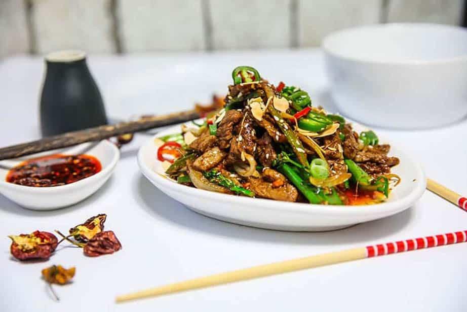 Sichuan Beef on a plate with chopsticks