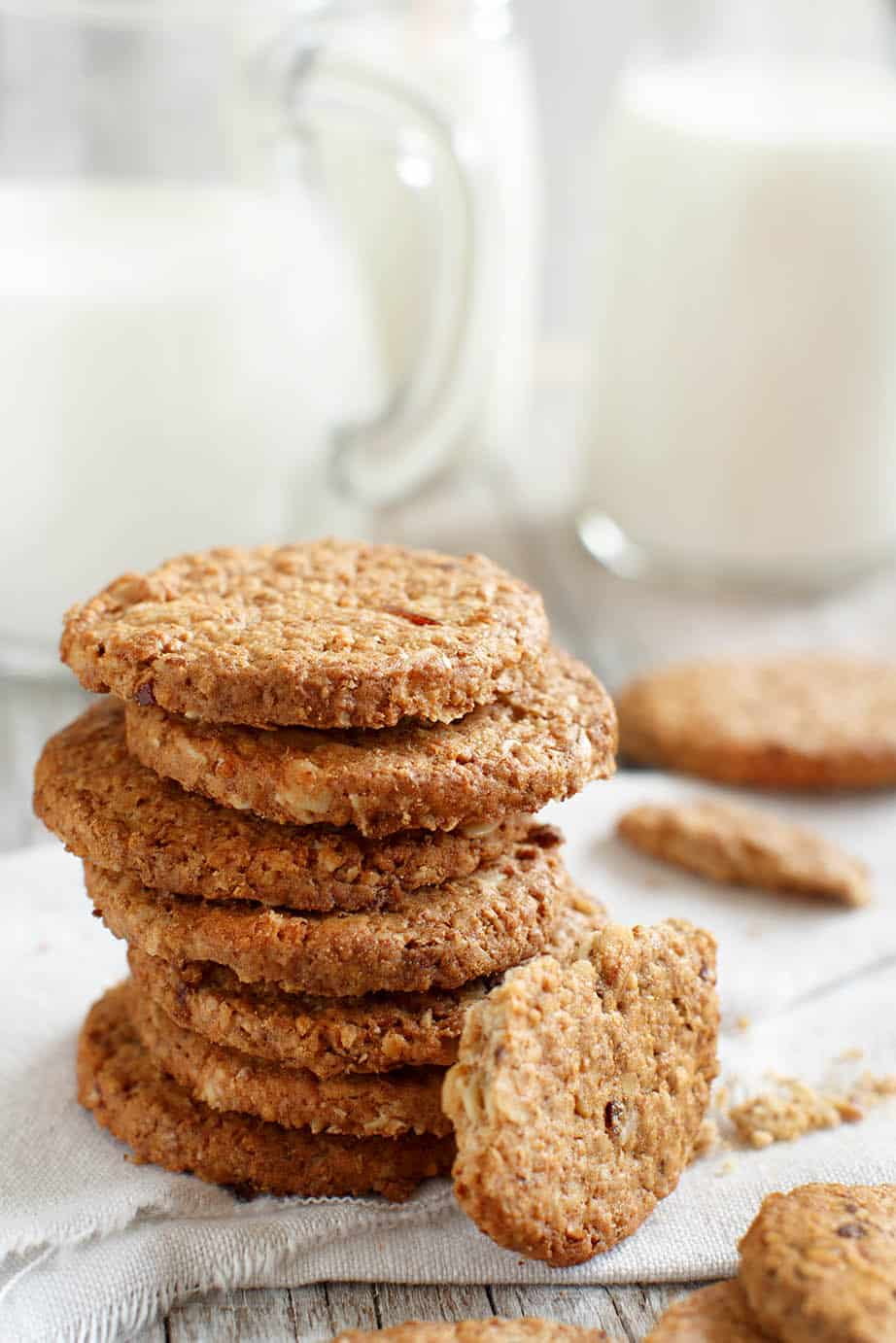 ANZAC biscuits stacked on a white background with a jug of milk