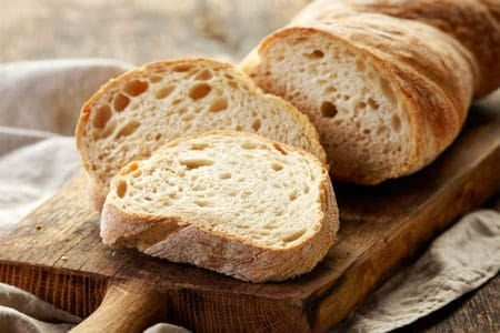 The image shows bread which has been proofed and baked on a cutting board