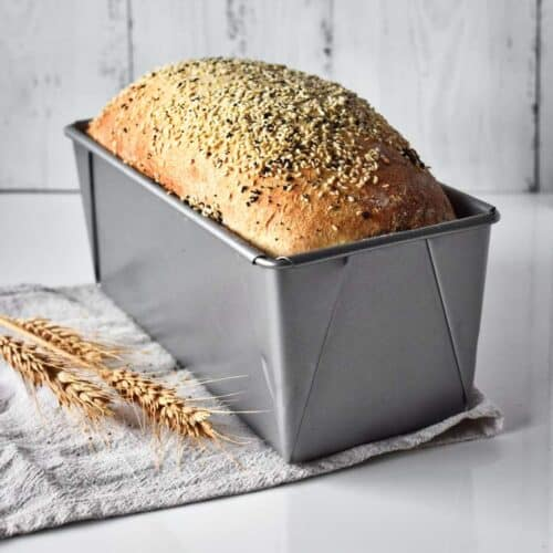 Seeded loaf of bread in a bread tin on the bench