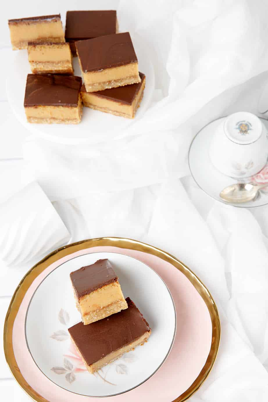 Overhead shot of caramel slice on a white background, pink plate