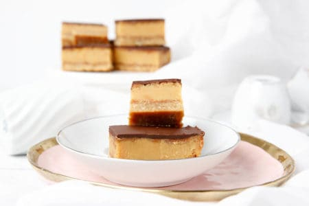 multiple caramel slices on a white and pink plate, light background