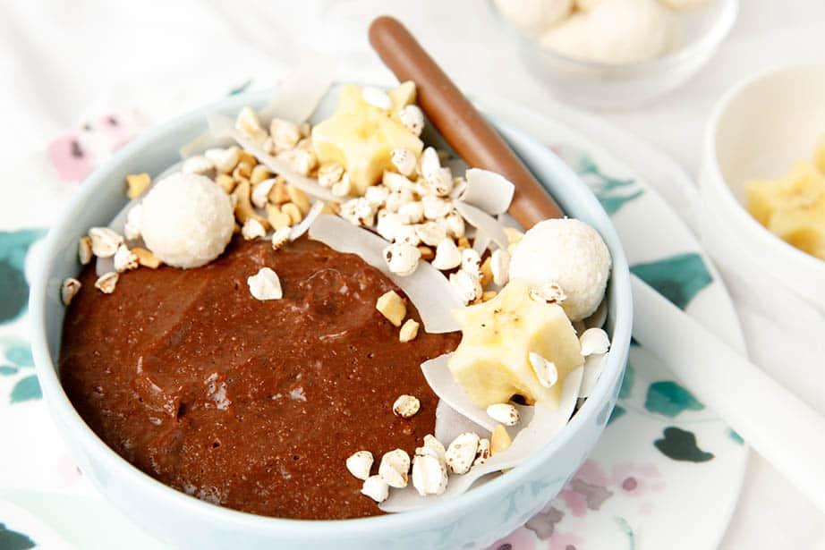 Landscape image of chocolate porridge with toppings on the side